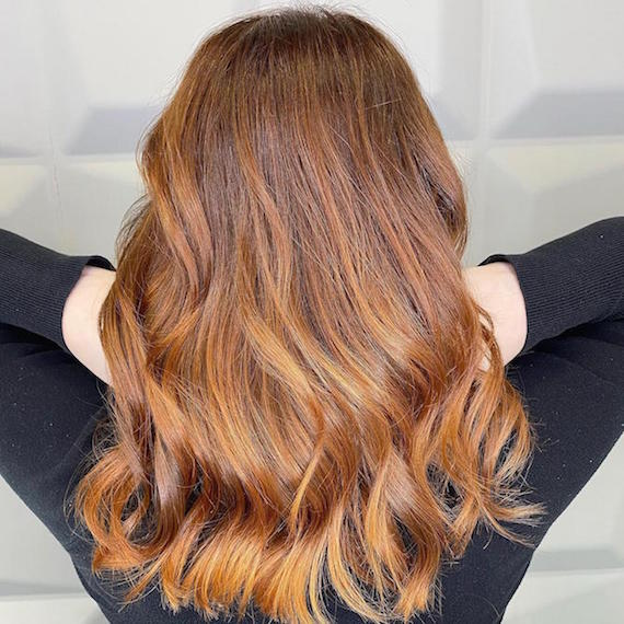 Back of woman's head with mid-length, wavy, copper ombre hair color, created using Wella Professionals.