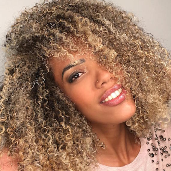 Woman looking into the camera with bouncy curly hair, cared for by Wella Professionals.