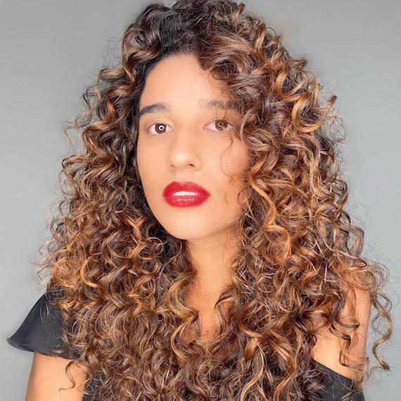 Woman wearing red lipstick with long, brown, curly hair, cared for by Wella Professionals.