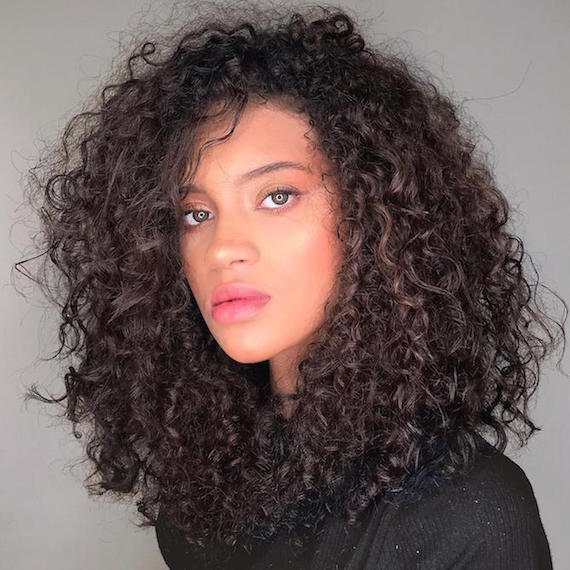 Woman with dark brown curly hair, cared for by Wella Professionals.