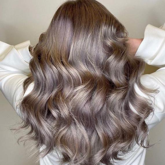 Back of woman's head with long, loosely curled, dark ash blonde hair, created using Wel-la Professionals.