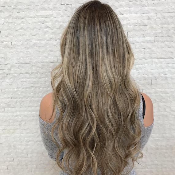 Image of the back of a woman's head with long, dark blonde hair and multi-tonal blonde babylights. Hair is styled in long, loose waves. Look created by Wella Professionals.