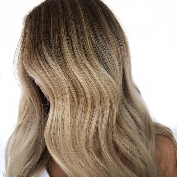 Image of a woman's side profile with dark blonde ombre color styled in loose waves. Look created by Wella Professionals.