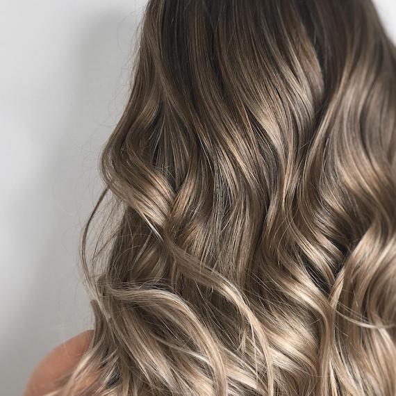 Image of the back of a woman's head with dark blonde balayage color styled in loose waves. Look created by Wella Professionals.