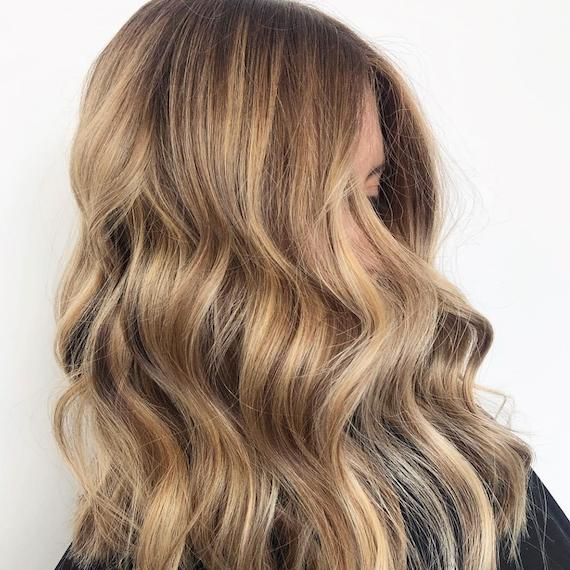Image of a woman's side profile with honeyed dark blonde hair color styled in loose waves. Look created by Wella Professionals.