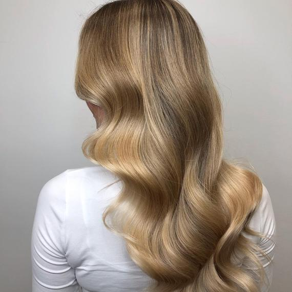 Image of the back of a woman's head with golden dark blonde hair color styled in soft waves. Look created by Wella Professionals.