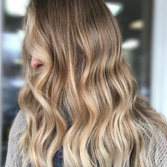Image of side profile of a woman with buttery dark blonde hair, styled in long, loose waves. Look created by Wella Professionals.
