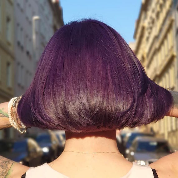Back of woman's head with short, dark purple hair, created using Wella Professionals.