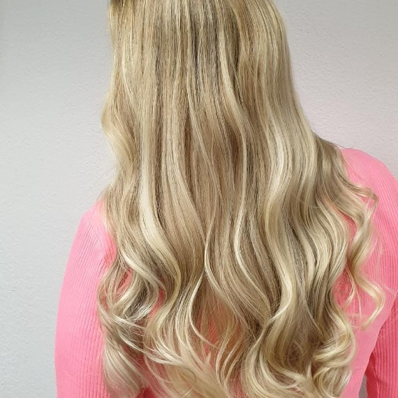 woman with long hair in sandy blonde balayage and light lowlights