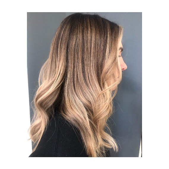 side portrait of woman with long blonde balayage and money piece hair