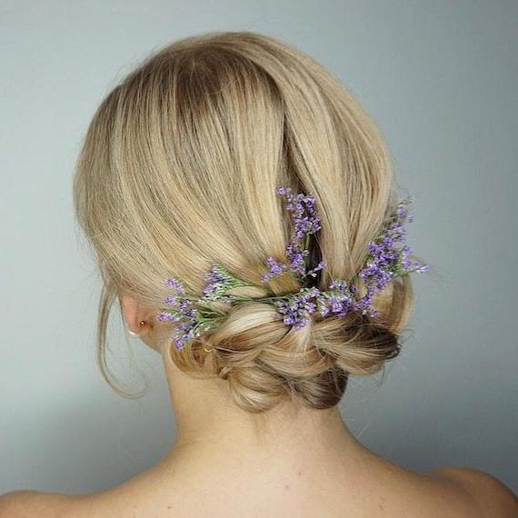 Back of woman's head with blonde hair in a low bun, accessorised with flowers.