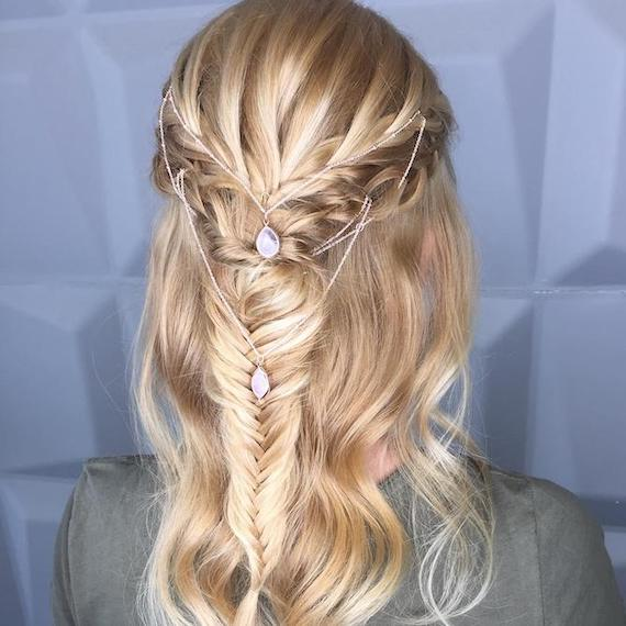 Back of woman's head with blonde hair, braids and a delicate hair accessory.