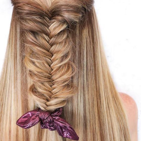 Back of woman's head with fishtail braid through hair, tied with a metallic scrunchie.