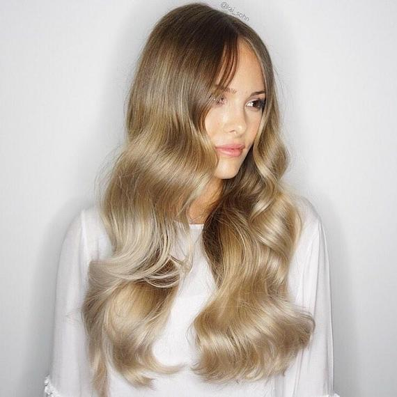 Photo of woman with very long, loosely curled hair and blonde foilyage, created using Wella Professionals.