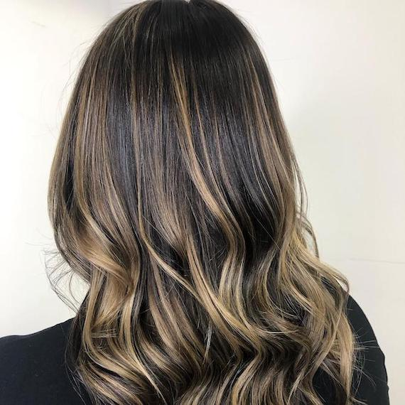 Back of woman's head with brunette hair and blonde foilyage, created using Wella Professionals.