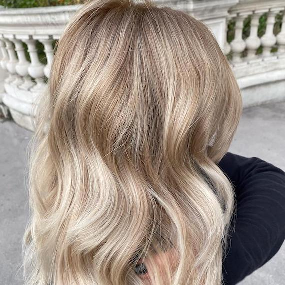 Back of woman's head with wavy hair and ivory blonde foilyage, created using Wella Professionals.