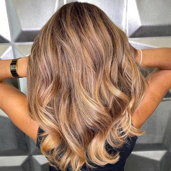 Back of woman's head with long, wavy, golden blonde hair and foilyage, created using Wella Professionals.