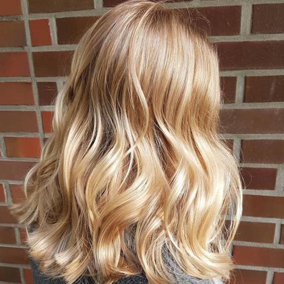 Side profile of woman with shoulder-length, light golden blonde hair, created using Wella Professionals.