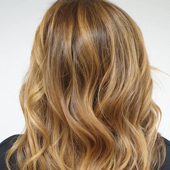 Back of woman's head with medium-length, medium golden blonde hair, created using Wella Professionals.