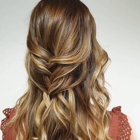 Back of woman's head with dark golden blonde hair in a half-up braid, created using Wella Professionals.