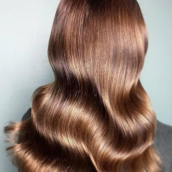 Photo of the back of a woman's head with long golden brown hair, created using Wella Professionals.