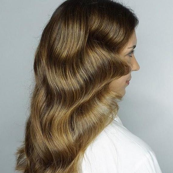 Side profile of woman with medium golden brown hair, created using Wella Professionals.