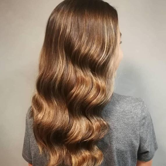 Photo of the back of a woman's head with golden brown babylights, created using Wella Professionals.