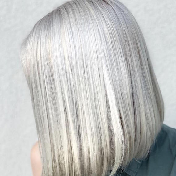 Side profile of woman with gray blonde bob, created using Wella Professionals.