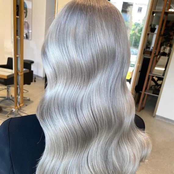 Back of woman's head with long, wavy, platinum gray blonde hair, created using Wella Professionals.