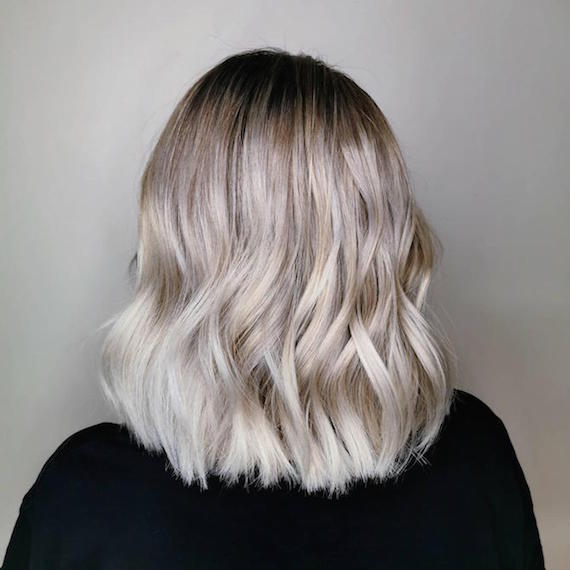 Back of woman's head with short, wavy gray blonde bob, created using Wella Professionals.