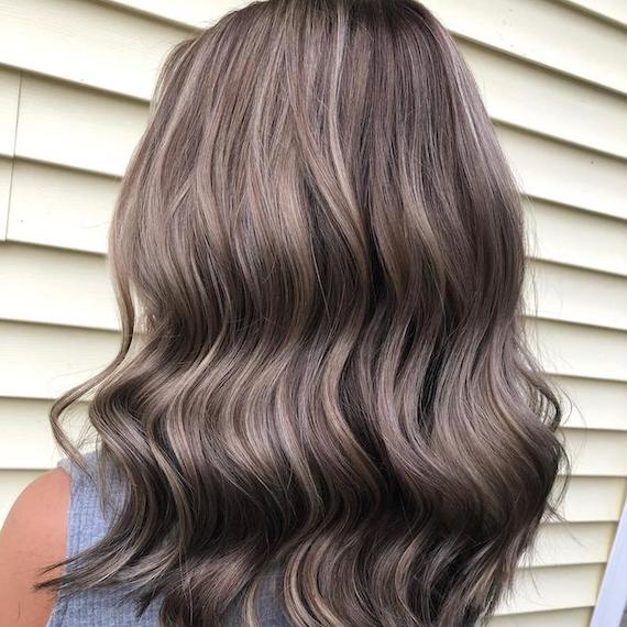 Back of woman's head with dark brown hair and gray highlights, created using Wella Profes-sionals.