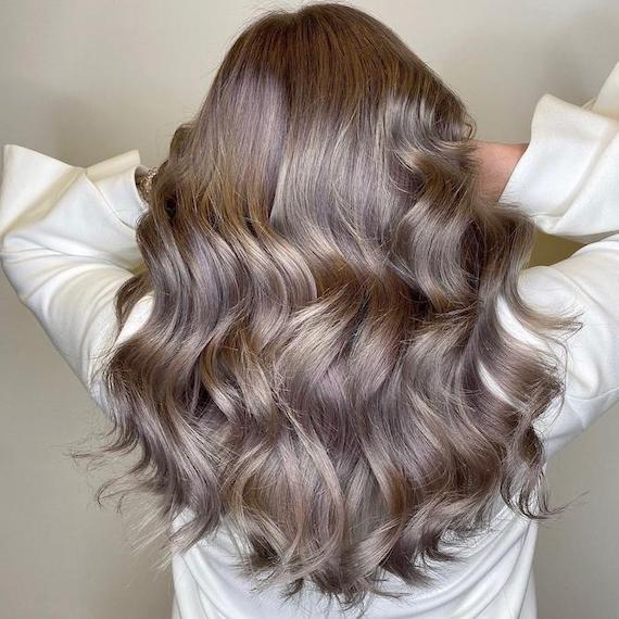 Back of woman's head with wavy, metallic, gray brown hair, created using Wella Profession-als.