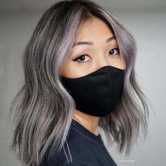 Woman wearing a black face mask. Her hair gray brown hair, created using Wella Profes-sionals, is styled in loose waves.