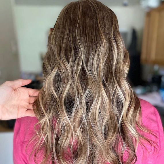 Back of woman's head with long, wavy hair after gray roots have been colored, created using Wella Professionals.