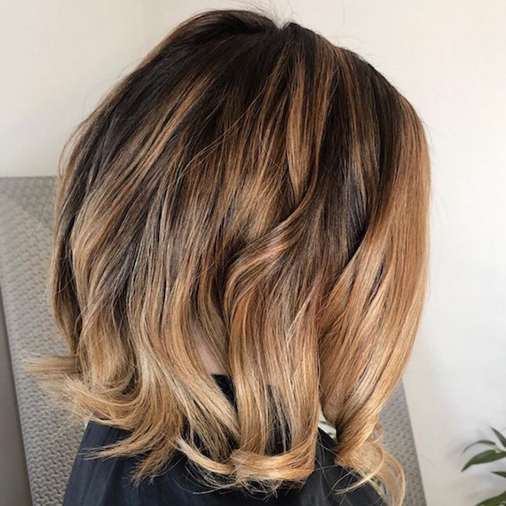 Side profile of woman after having dark gray roots coloured using Wella Professionals.