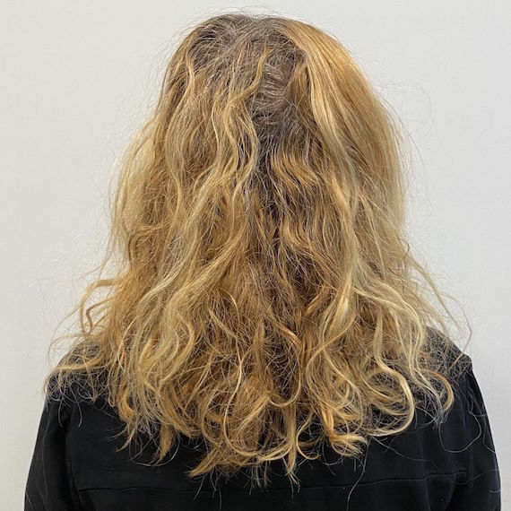 Photo of wavy blonde hair with gray roots.