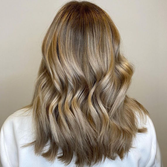 Back of a woman's head with mid-length, glowy, dark blonde hair, created using Wella Professionals.