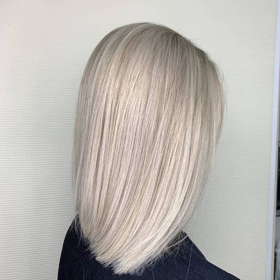 Side profile of woman with straight, ice blonde bob, created using Wella Professionals.