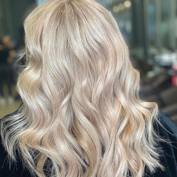 Back of a woman's head with long, wavy, platinum blonde hair, created using Wella Professionals.