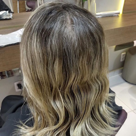 Back of woman's head with wavy blonde hair and gray roots.