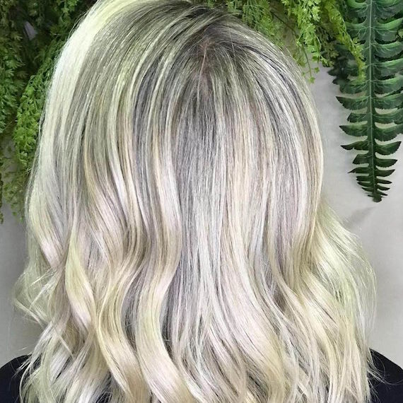 Back of woman's head with blonde highlights over gray roots, created using Wella Professionals.