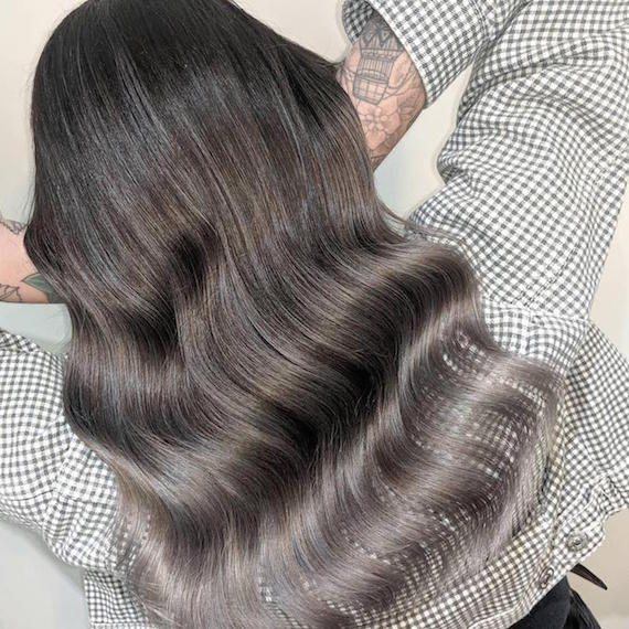 Back of woman's head with long, wavy, black to gray ombre hair, created using Wella Professionals.