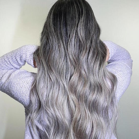 Back of woman's head with long, wavy, black to silver ombre hair, created using Wella Professionals.