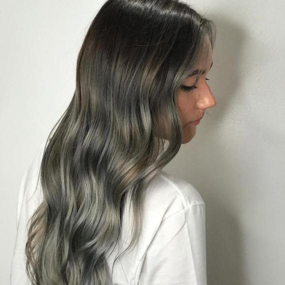 Side profile of woman with dark roots and long gray ombre hair, created using Wella Professionals.