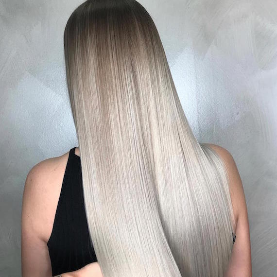 Back of woman's head with long, straight, gray blonde ombre hair, created using Wella Professionals.