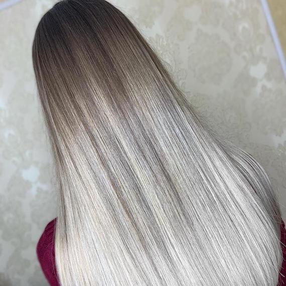 Back of woman's head with long, straight, light gray ombre hair, created using Wella Professionals.