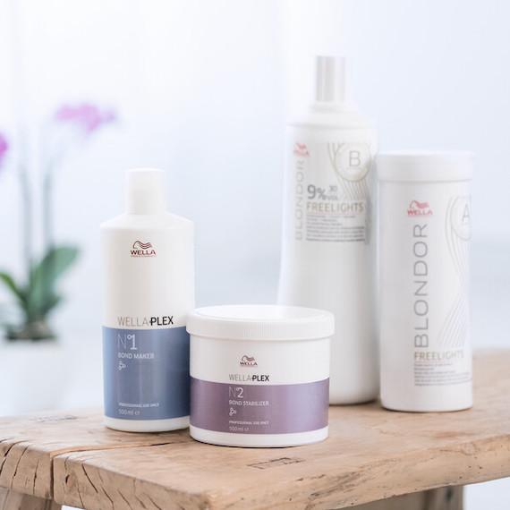 Bottles of Wella Professionals WellaPlex and Blondor lightening products on a wooden table.