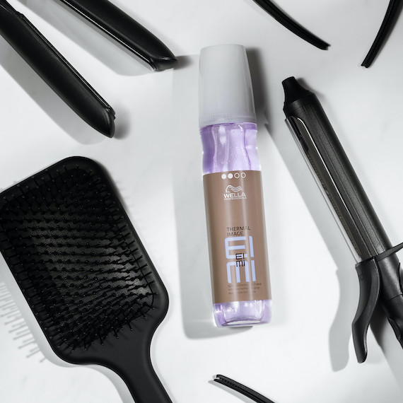 Wella Professionals EIMI Thermal Spray on a white surface, surrounded by hair styling accessories.