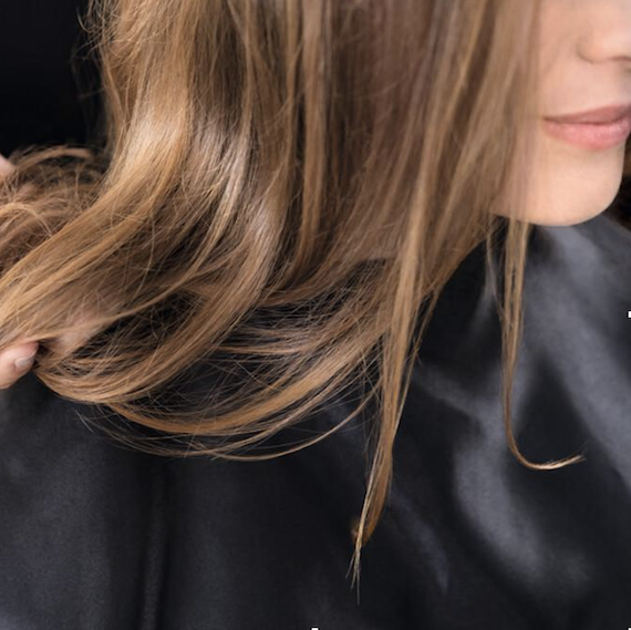 Close-up of woman's brown hair as she wears a black salon gown.