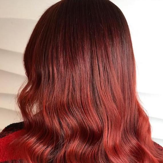 Photo of the back of a woman's head with red hair, glossed using Wella Professionals